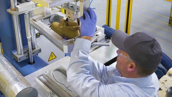 A BASF employee pulls a shoe out of the mold on a GUSBI machine. Footwear Development Center in Wyandotte, Michigan / Ein BASF-Mitarbeiter an GUSBI-Maschine einen Schuh aus der Form. Footwear Development Center in Wyandotte, Michigan